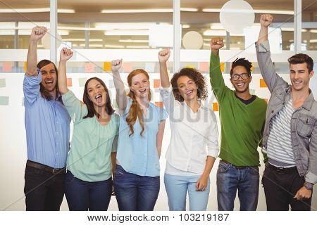 Portrait of excited business people with arm raised in office