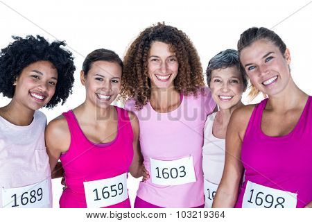Portrait of smiling female athletes with arms around while standing against white background