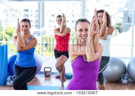 Attractive women doing eagle pose in fitness studio