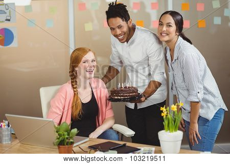 Portrait of smiling businesswoman celebrating birthday with colleagues in office