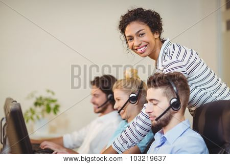 Portrait of smiling businesswoman with employees in call center