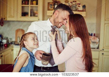 Happy couple and their daughter in the kitchen