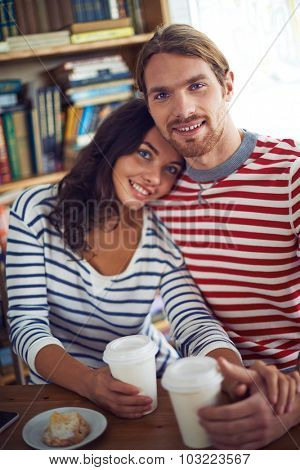 Amorous sweethearts sitting in cafe