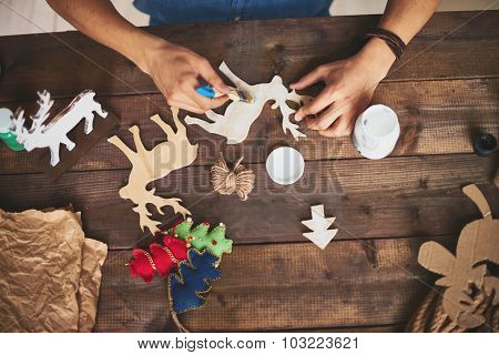 Male hands with paintbrush painting wooden toy deer with gouache
