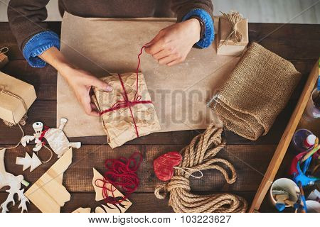 Hands of man tying up wrapped gift with woolen thread