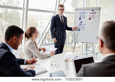 Young employee by whiteboard explaining data to group of managers during presentation