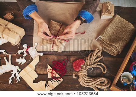 Hands of man tying up xmas gift wrapped into paper