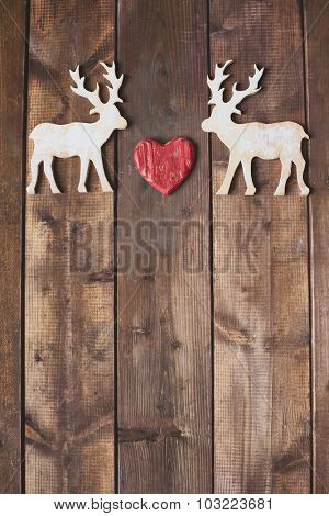 Toy reindeers with heart between them on wooden background