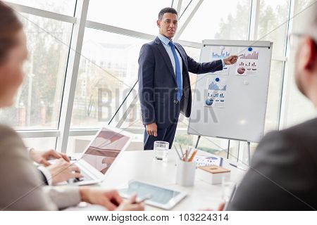 Successful businessman standing by whiteboard and pointing at chart on paper while looking at colleagues