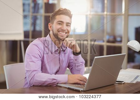 Portrait of handsome businessman with hand on chin working on laptop in creative office