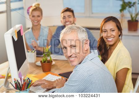 Portrait of happy business people sitting by desk with computer in creative office