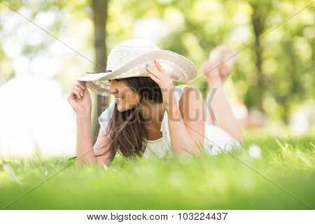 Thoughtful happy young woman holding sun hat while lying on grassland in park