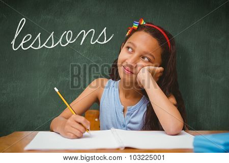 The word lessons and cute pupil at desk against green chalkboard