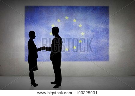 Silhouettes shaking hands against eu flag