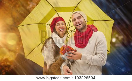 Autumn couple holding umbrella against autumn changing to winter