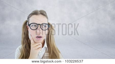 Female geeky hipster looking confused against grey wall