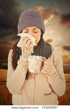 Sick brunette blowing her nose while holding a mug against country scene