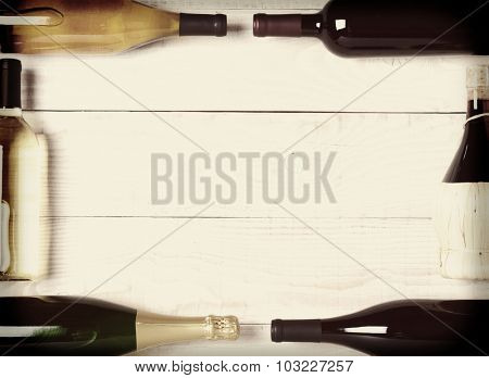 Retro High angle shot of wine bottles on a rustic white wood table. The bottles are laying on their sides and end to end to form a rectangle frame with a blank center with faded instagram feel.