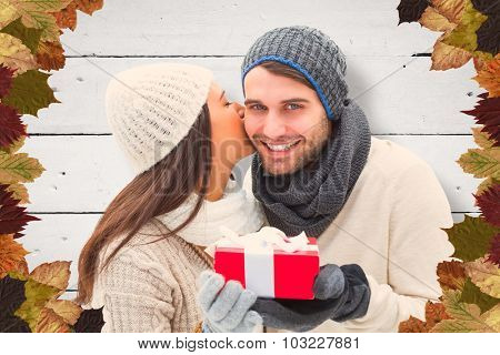 Winter couple holding gift against white wood