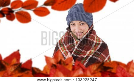 Smiling brunette with checked blanket against autumn leaves
