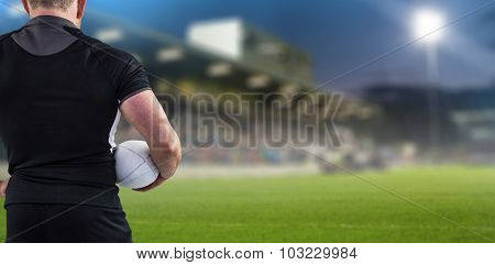 Rugby player holding the ball against pitch and stands