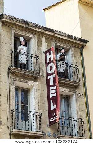 Sign Hotel At An Old Facade In Red Letters In Aix En Provence And A Statue Of A Cook At The Balcony,