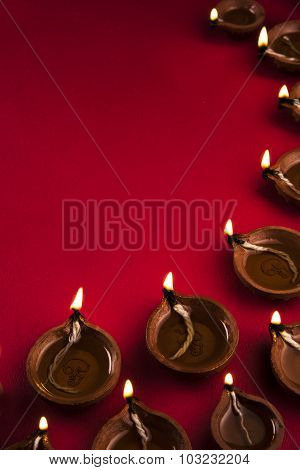 many beautiful diwali diya together on a red background, diwali greeting