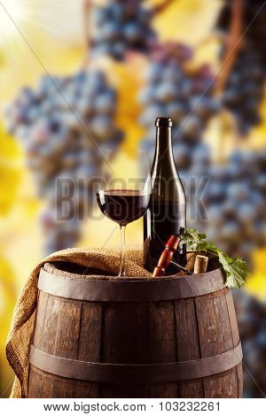 Red wine bottle and glass on wooden keg. Grapes of wine on background
