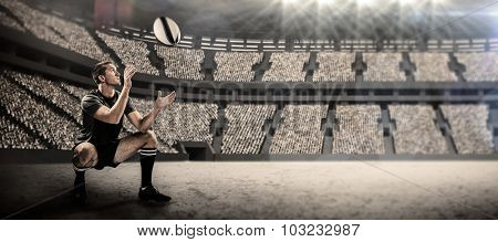 Full length of rugby player catching the ball against stadium
