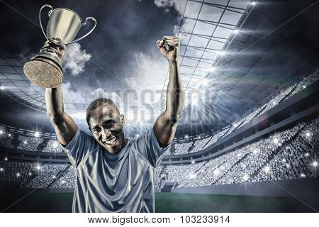 Portrait of happy sportsman cheering while holding trophy against football stadium with fans in white