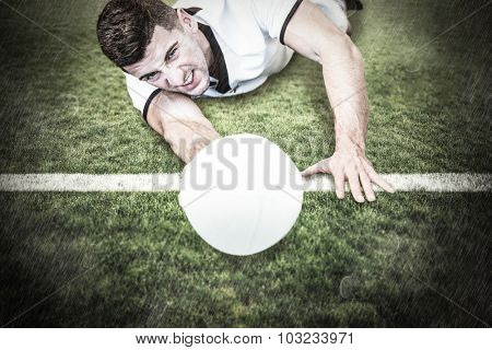 Man lying down while holding ball against rugby pitch
