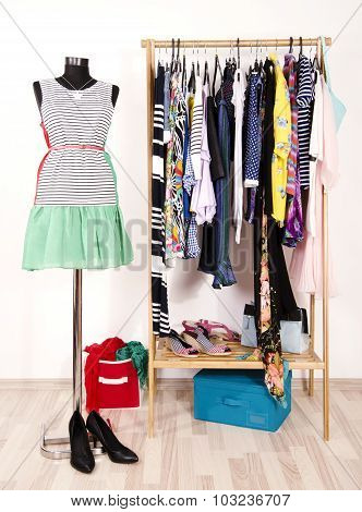 Dressing Closet With Colorful Clothes Arranged On Hangers And A Summer Outfit On A Mannequin.