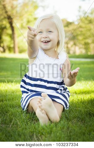 Cute Little Girl Sitting and Laughing in the Grass Outside.