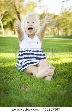 Cute Little Girl with Thumbs Up in the Grass Outside.