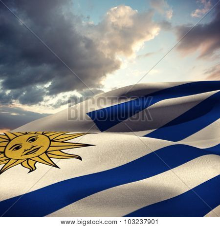 Waving Uruguayan flag against blue and orange sky with clouds