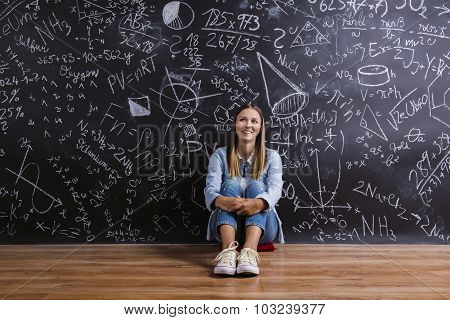 Beautiful young girl in front of blackboard