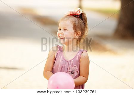 Portrait Of Laughing And Playing A Little Girl Holding A Balloon