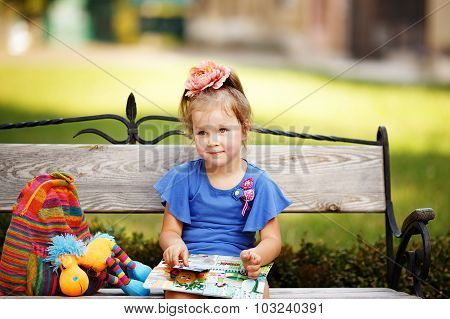 Portrait Of A Little Girl Reading A Children's Book On A Park Bench