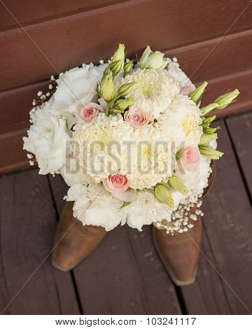 bridal bouquet sitting on top of cowgirl boots