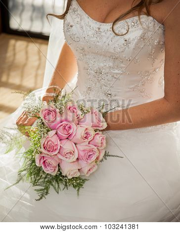 bride sitting, laying her large bouquet of pink roses on her lap