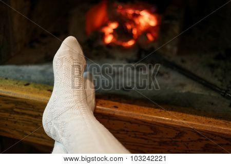 Feet In Wool Socks Warming At Fireplace