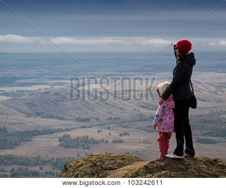 Woman And Child Standing On A Mountain