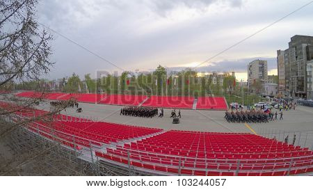 SAMARA - MAY 06, 2015: Rows of soldiers march between empty tribunes at spring evening. Aerial view video frame