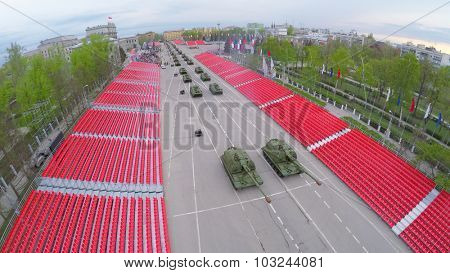 SAMARA - MAY 06, 2015: Military hardware moves along empty tribunes during parade rehearsal at spring evening. Aerial view video frame