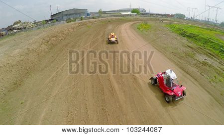 SAMARA - MAY 24, 2015: Three small racing cars ride by ground track at spring sunny day. Aerial view video frame