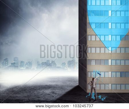 Businesswoman painting a high office building in blue color