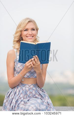 Smiling lady with a book outdoors