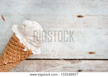 Single vanilla ice cream in a waffle cones over wooden background.