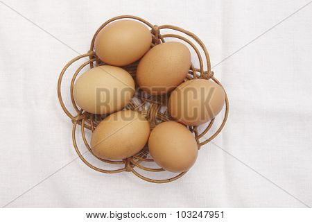 Brown Eggs Over A Wicker Basket With White Tablecloth Background