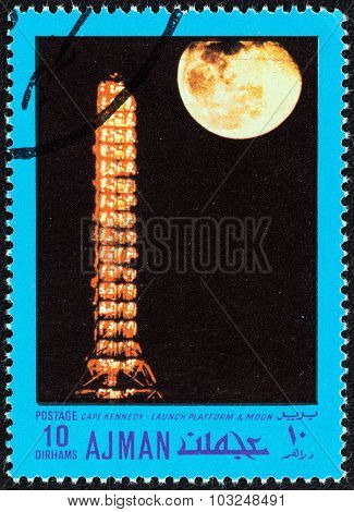 AJMAN EMIRATE - CIRCA 1970: Stamp shows Cape Kennedy, launch platform and moon